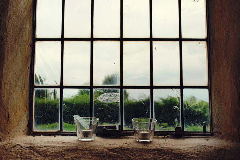 Okno v hlinenej budove, dve sviečky na parapetnej doske